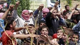 Syrians shout slogans in favour of Turkey as they wait to cross from the Syrian side of the border