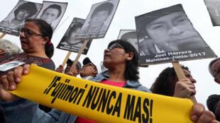 Les manifestants portent les photos de victimes dans les années 80-90 lors d'une marche à Lima après l'annonce de la grâce présidentielle accordée à Alberto Fujimori, le 25 décembre 2017.