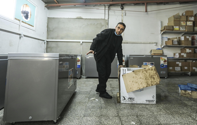 Un trabajador sanitario palestino abre una de las primeras cajas con vacunas contra el Covid-19 de Sputnik V, en Gaza, el 17 de febrero de 2021