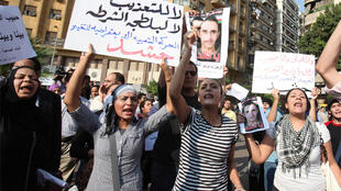 """Protestors in Cairo hold up a banner saying """"no to torture and no police brutality"""" and a photo of Khaled Said"""