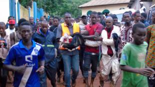 Les secours transportent une petite fille rescapée après l'effondrement d'une décharge sur des habitations, dans la banlieue de Conakry, le 22 août 2017.
