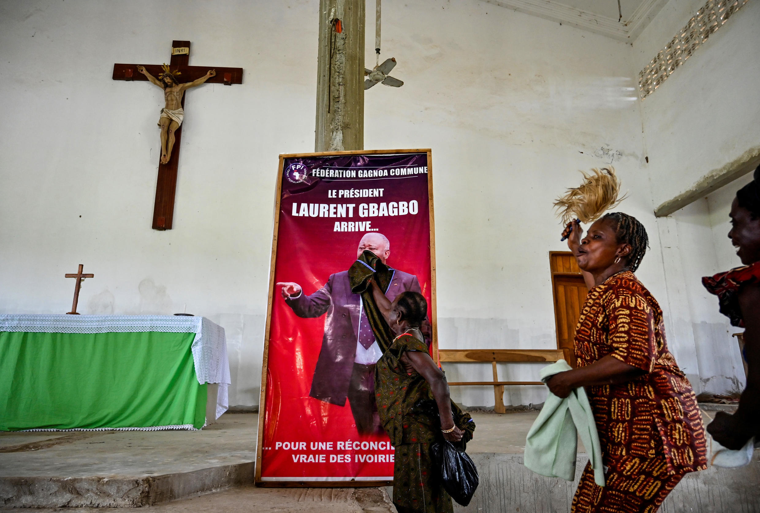 A woman dusts a poster reading 'President Laurent Gbagbo arrives for a true reconciliation of Ivorians' before a mass in his hometown of Mama