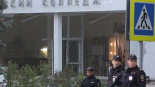 Des policiers russes se rassemblent devant le bâtiment endommagé d'un collège à la suite d'un attentat récent dans la ville de Kertch.