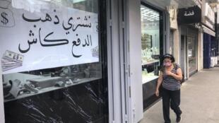 Une femme passe devant une bijouterie de Beyrouth qui indique racheter de l'or et payer en dollars le 6 juillet 2020.