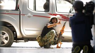 Lors du conflit libyen, un rebelle crie à un journaliste de se mettre à couvert. Tripoli, le 25 août 2011.