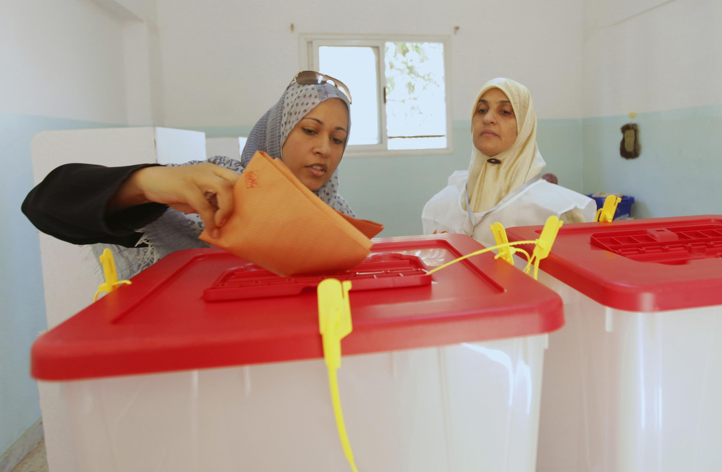 A woman casts her vote at a polling station during the National Assembly election in Benghazi, 7 July, 2012