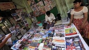 Vendors sit at a roadside newspaper and journals shop in Yangon