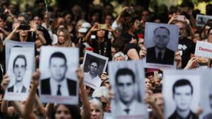 Des manifestants brandissent des portraits de victimes de la dictature lors d'une mobilisation le 31mars 2019.
