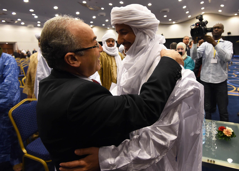 Le ministre algérien des Affaires étrangères Ramtane Lamamra donne l'accolade au secrétaire général du MNLA, Bilal Ag Acherif, lors de la cérémonie de paraphe de l'accord d'Alger, le dimanche 1er mars 2015.
