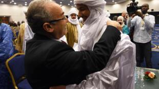 Le ministre algérien des Affaires étrangères Ramtane Lamamra donne l'accolade au secrétaire général du MNLA, Bilal Ag Acherif, lors de la cérémonie de paraphe de l'accord d'Alger, le 1er mars 2015.
