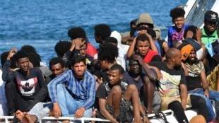 Des migrants de Tunisie et de Libye arrivent à bord d'un bateau des garde-côtes sur l'île italienne de Lampedusa, le 1er août 2020.