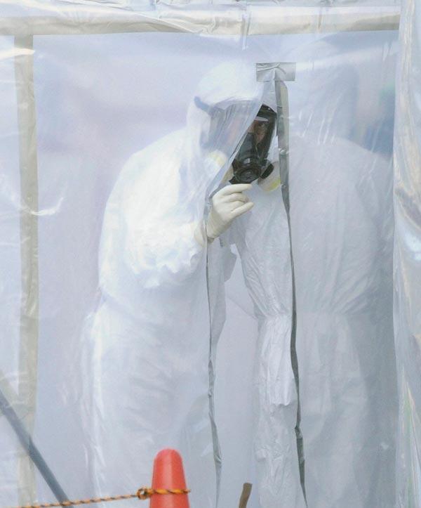 A proximité d'un supermarché de Tokyo, un employé porte un habit de protection pour déplacer du matériel radioactif destiné à être incinéré (1er novembre 2011).