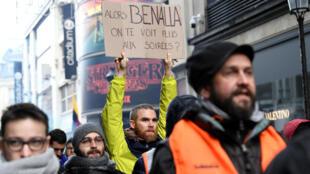 Un homme porte une pancarte sur laquelle il est écrit: «Alors Benalla, on ne te voit plus aux soirées ?» lors d'une journée nationale de protestation du mouvement «Gilets jaunes» à Paris, le 8 décembre 2018.