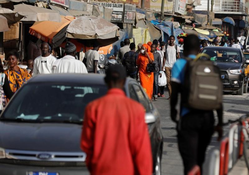 Une femme porte un masque en raison de l'épidémie mondiale de coronavirus alors qu'elle se promène dans une rue commerçante animée de Dakar, au Sénégal, le 18 mars 2020.