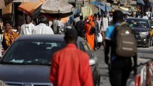 Une femme porte un masque, en raison de l'épidémie mondiale de coronavirus, alors qu'elle se promène le long d'une rue commerçante animée de Dakar, au Sénégal, le 18 mars 2020.