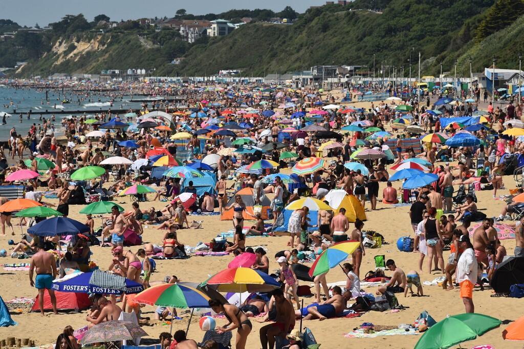 Em plena pandemia de coronavírus, britânicos invadiram o litoral e esqueceram das medidas de proteção contra a doença. Na foto, a praia de Bournemouth, no sul da Inglaterra, nesta quinta-feira (25).