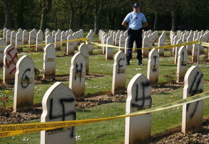 Túmulos de muçulmanos de um cemitério militar no norte da França são pichados com símbolos nazistas.