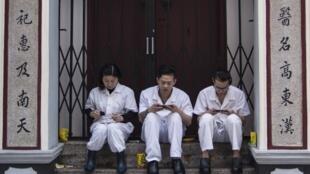 Des employés chinois d'un restaurant avec leur smartphone pendant leur moment de pause.