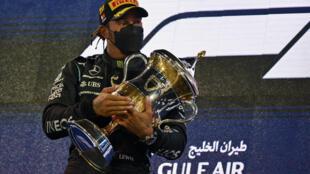 El piloto británico de Mercedes, Lewis Hamilton, sostiene el trofeo del ganador en el podio después del Gran Premio de Fórmula Uno de Baréin en el Circuito Internacional de Baréin, en la ciudad de Sakhir, el 28 de marzo de 2021.