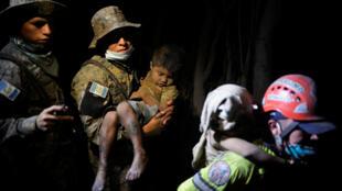 Soldados resgatam crianças depois da erupção do Vulcão de Fogo, na Guatemala, em 3 de junho de 2018.