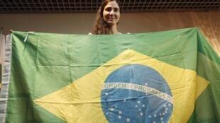 A dissidente cubana Yoani Sanchez posa com uma bandeira do Brasil em sua chegada no aeroporto internacional de Guararapes, em Recife, nesta segunda-feira (18).