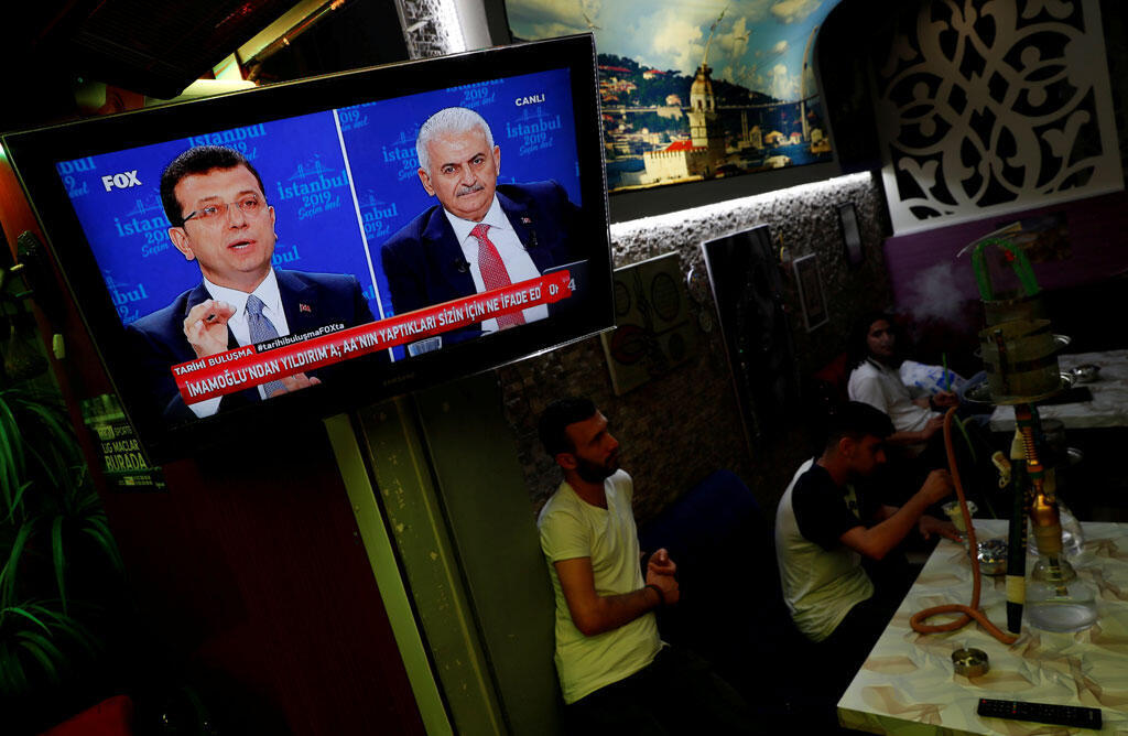 Des gens regardent un débat télévisé entre le candidat à la mairie d'Istanbul, Ekrem Imamoglu (G), du Parti républicain du peuple (CHP), et Binali Yildirim (D), du Parti AK (AKP), dans un café du centre d'Istanbul, en Turquie, le 16 juin 2019.