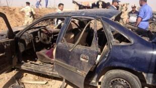 Ciudadanos iraquíes rodean los restos de un auto destruido tras una explosión a 15 km de Kirkuk.