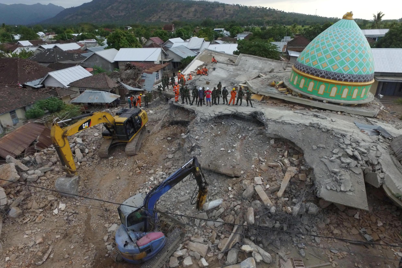 Vision aérienne de la mosquée Jamiul Jamaah, effondrée lors du séisme, où des soldats et des pompiers cherchent des survivants et des victimes à Pemenang, au nord de Lombok, le 8 août 2018.