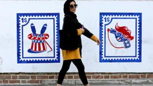 Une femme passe devant les peintures murales de l'ancienne ambassade américaine à Téhéran, le 20 septembre 2020.