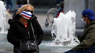 A woman wearing a protective face mask depicting the French flag talks with a friend near a fountain in Lille, after France begun a gradual end to a nationwide lockdown due to Covid-19, 11 May 2020.