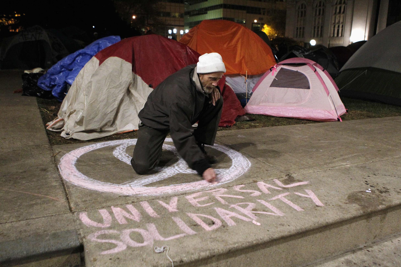 A camper draws a symbol at the Occupy Oakland campsite