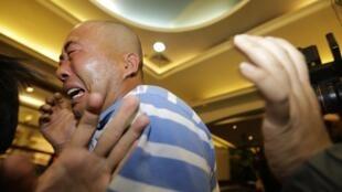 A Pékin, les proches des 239 passagers du vol MH370 de la Malaysia Airlines éclatent en sanglots après la retransmission à la télévision de la conférence de presse de Najib Razak, le Premier ministre malaisien.