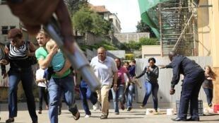Un officier de police tient son arme à la main tandis que les clients fuient la fusillade. Westgate shopping mall, Nairobi, le 21 septembre 2013.