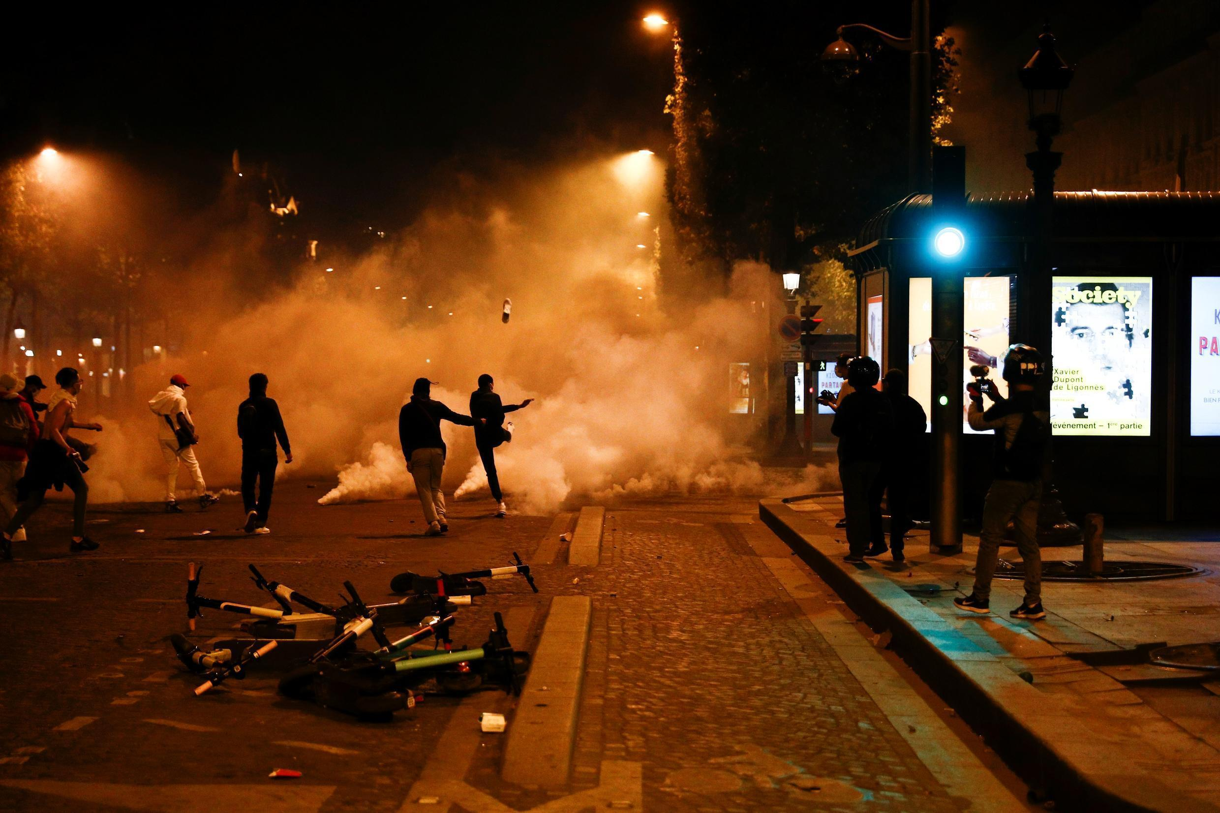 Police fire tear gas on PSG supporters on the Avenue des Champs-Elysées, on 23 August, 2020, following the team's defeat in the Champions League final.