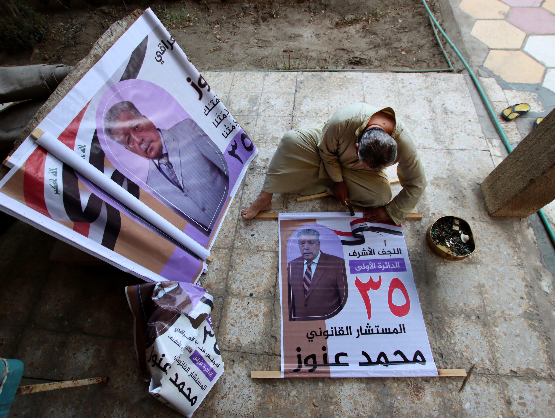 Un candidato independiente iraquí cuelga sus propios carteles electorales cerca de la ciudad de Nayaf (centro de Irak), el 6 de octubre de 2021