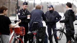 En France, des policiers contrôlent des passants afin de vérifier qu'ils soient munis de justificatifs de déplacement. Les forces de police procéderont à ces vérifications pendant toute la durée de confinement, en vue de ralentir la propagation du virus.
