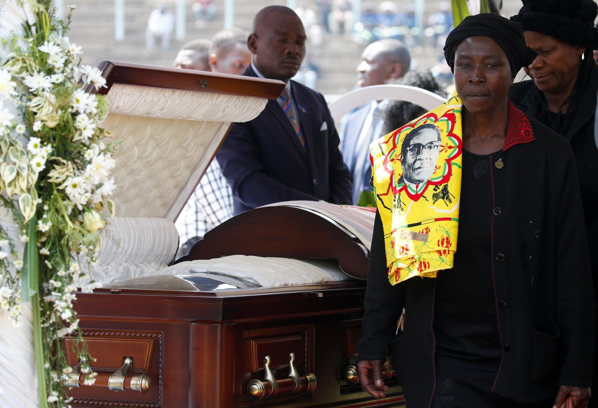 A mourner with a regalia bearing the face of Mugabe, walks after paying her last respects to Robert Mugabe's body as it lies in state at the at Rufaro stadium, in Harare, Zimbabwe, September 13, 2019