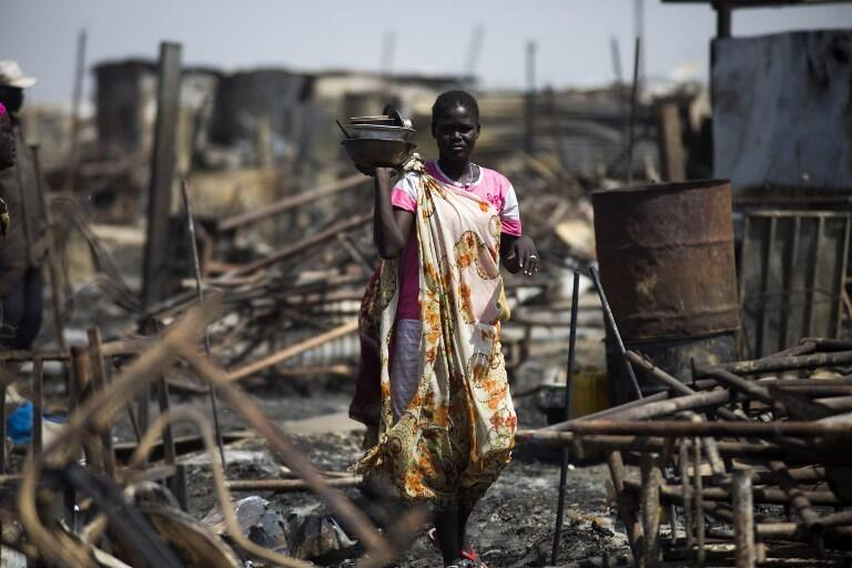 Woman searches for her belongings in an area that had been burnt and looted, Malakal, 26 February 2016.