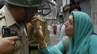 A Kashmiri Muslim woman confronts an Indian police officer during the protests