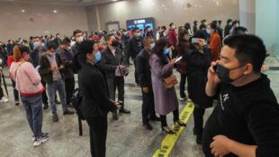 La gente hace cola para comprar billetes de tren en la estación ferroviaria de Yichang Este, el 25 de marzo de 2020 en la ciudad china de Yichang, en la provincia de Hubei
