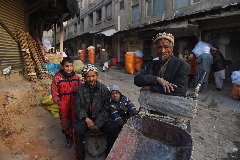 Des afghans attendent le marché dans les rues de Kaboul, en novembre 2014.
