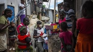 Des membres du personnel de la Croix-Rouge kenyane livrent des désinfectants pour les mains aux résidents pour freiner la propagation du coronavirus COVID-19 dans le bidonville de Mathare à Nairobi, au Kenya, le 1er mai 2020.