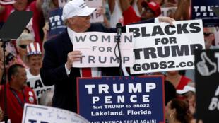 Donald Trump, une pancarte «Les femmes avec Trump» dans les mains, lors d'un meeting à Lakeland, le 12 octobre 2016.
