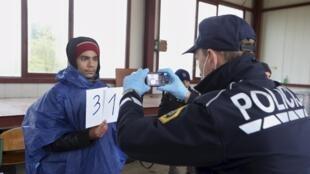 Um migrante é registrado e fotografado pela polícia ao entrar na Eslovênia neste sábado, 17 de outubro de 2016.