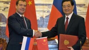 Le président russe Dmitri Medvedev (g) et le président chinois Hu Jintao se serrent la main, au Palais de l'Assemblée du Peuple, à Beijing le 27 septembre 2010.