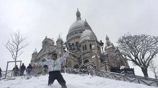 A skier hits the slope in front the Sacré Coeur cathedral