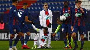 La star du PSG Neymar au sol contre Caen devant son coéquipier Leandro Paredes en Coupe de France, le 10 février 2021 à Caen