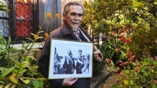 Jocelyn Rafidinarivo, dans son jardin, en juin 2020. Dans ses mains, un cliché datant des années 60 où il tend le micro à des enfants, sous l'oeil du président Philibert Tsiranana.