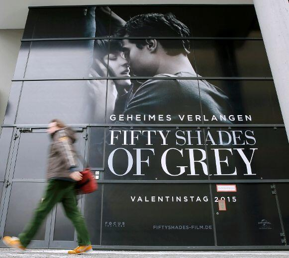 """A pedestrian walks past an advertising placard for the first movie in the """"Fifty Shades..."""" series"""