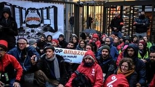 "Attac movement activists hold signs reading ""Stop Amazon and its world"" during an anti Black Friday action in front of the Amazon France headquarters in Clichy, north of Paris, early on November 29, 2019."
